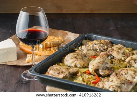 Chicken  baked in a pan with potatoes and apples. On a brown wooden background. - stock photo
