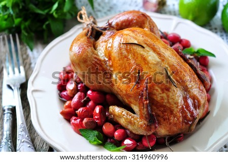 chicken baked with dogwood, garlic and rosemary on a wooden table - stock photo