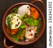 Chicken bouillon with vegetables and spices in a ceramic pot. - stock photo