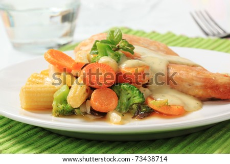 Chicken breast and mixed vegetables poured with cream sauce - stock photo
