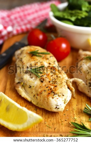 Chicken breast baked with rosemary on a cutting board.
