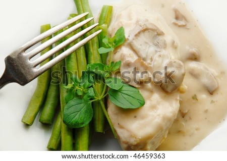 Chicken breast in mushroom sauce with green beans close up from above.