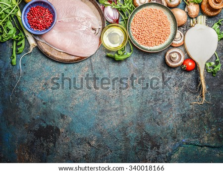 Chicken breast, red lentil, fresh vegetables and various ingredients for cooking on rustic background, top view. Horizontal border. Healthy food, diet or clean eating concept - stock photo