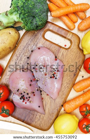 Chicken breast vegetable tomato potato carrot broccoli lemon on chopping block with copy space