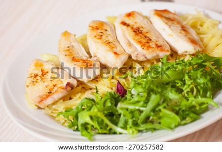 chicken breast with pasta and salad - stock photo