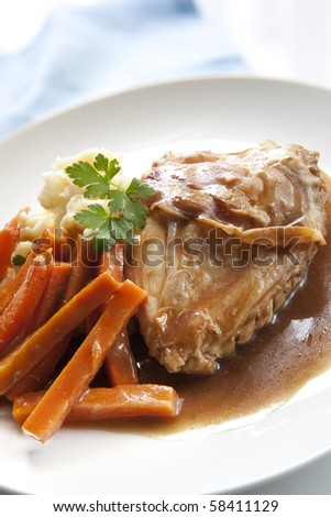 Chicken breast with prosciutto, served with mashed potato, carrot sticks, and topped with a delicious sauce. - stock photo