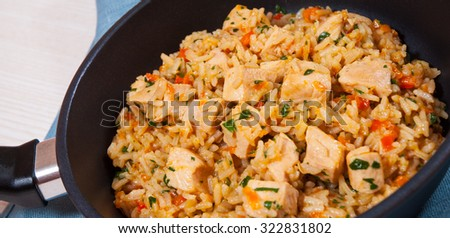 Chicken Breast with Rice and vegetables in a frying pan - stock photo