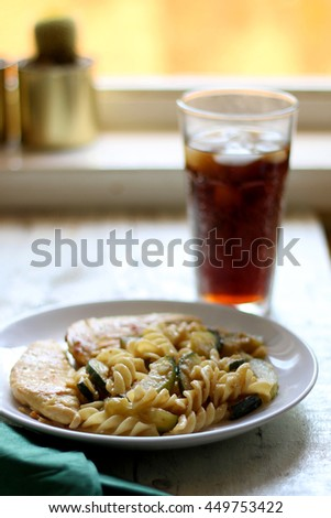 Chicken breasts, pasta and zucchini with melted cheese. Soda with ice in the background. Selective focus.  - stock photo