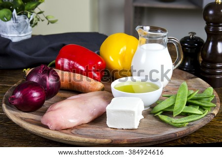Chicken breasts with fresh healthy  vegetables, oil and spices.  Raw products on the wooden background  - stock photo