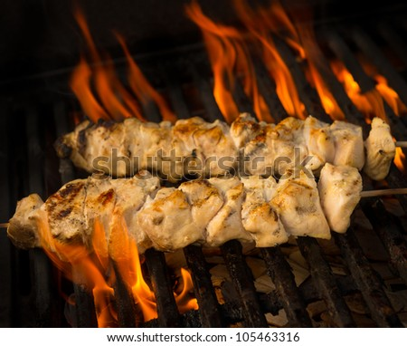 Chicken brochette cooking on a barbecue grill with flame and fire. Shallow depth of field. - stock photo