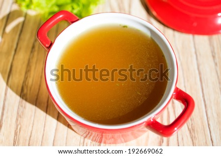 Chicken broth, bouillon, clear soup in a cup next to fresh herbs. - stock photo