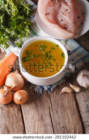 Chicken broth in a bowl and ingredients on the table close-up. vertical - stock photo