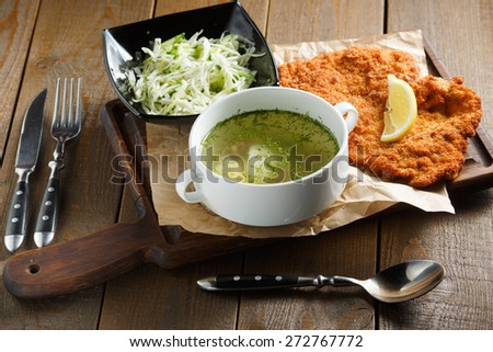 Chicken broth with egg, fried meat in batter, lemon and fresh salad on a brown wooden background, view from the top - stock photo