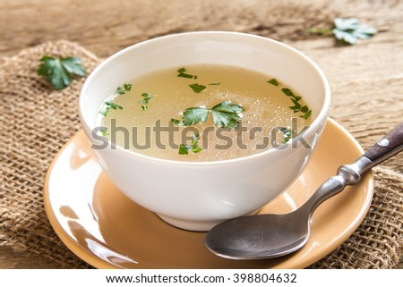 Chicken broth with parsley in white bowl close up - stock photo