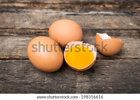 Chicken brown eggs and broken egg on wooden background - stock photo