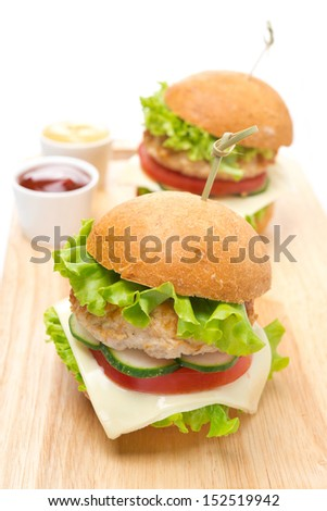 chicken burger with vegetables, cheese, ketchup and mustard on a wooden board, close-up