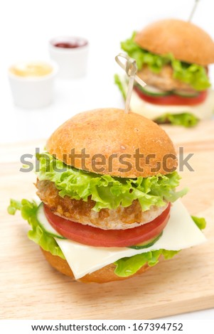chicken burger with vegetables, cheese on a wooden board, close-up - stock photo