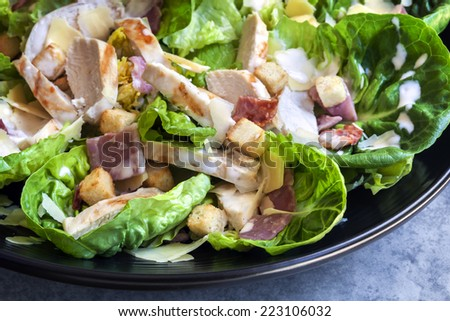 Chicken caesar salad on black plate. - stock photo