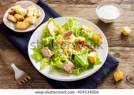 Chicken caesar salad with cheese and croutons over rustic wooden background  - stock photo