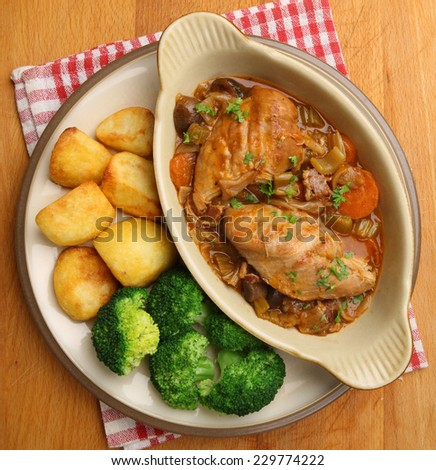 Chicken casserole served with roast potatoes and broccoli. - stock photo
