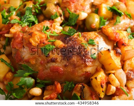 Chicken casserole with potatoes, beans, tomatoes, olives and parsley. Close up, horizontal shot - stock photo