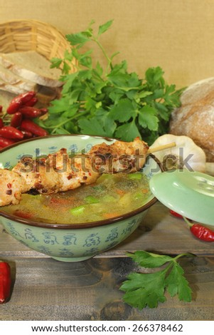 Chicken consomme with chicken skewers, vegetable and greens - stock photo
