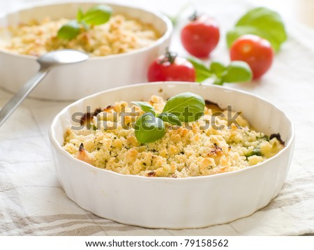 Chicken crumble with basil and tomato on background. Selective focus