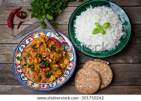 Chicken curry tikka masala with basmati rice on decorated bowl
