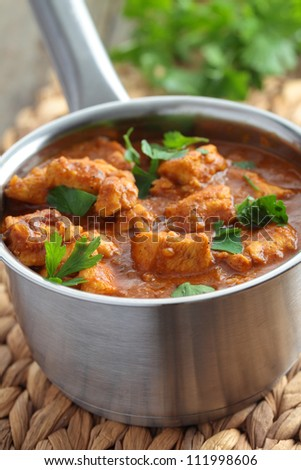 Chicken curry with parsley in a saucepan - stock photo
