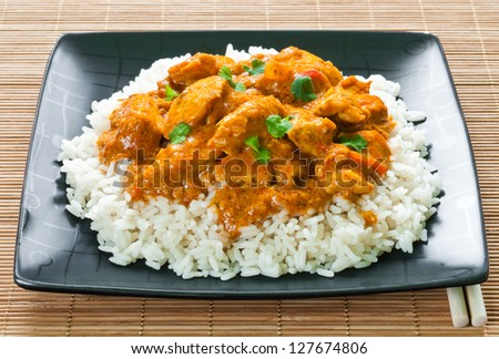 Chicken curry with rice and chopsticks on place mat - stock photo
