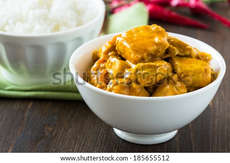 Chicken curry with rice in white bowl on wooden table - stock photo