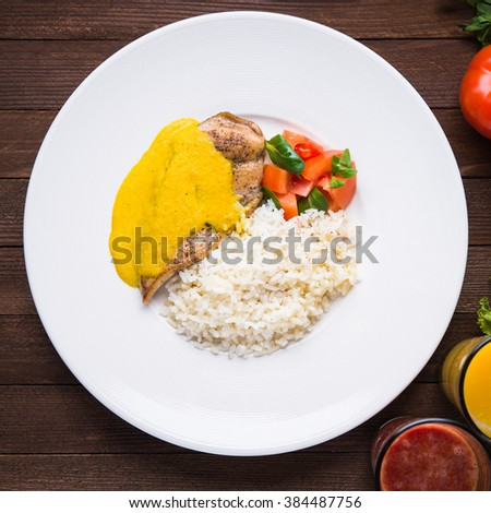 Chicken curry with white rice and vegetables in a plate on dark wood background top view. Asian food. - stock photo