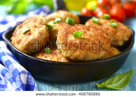 Chicken cutlets in a skillet on a blue wooden background. - stock photo