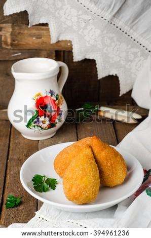 Chicken cutlets in breadcrumbs on Kiev (Chicken Kiev) in white bowl on wooden background. Ukrainian cuisine. Selective focus - stock photo
