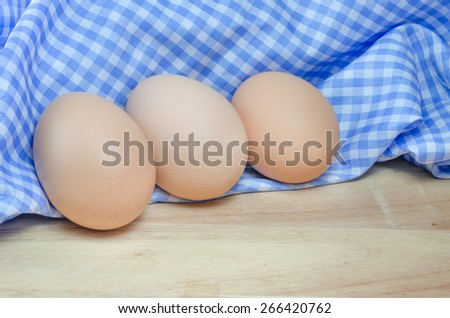 Chicken egg with blue cloth on wodden table