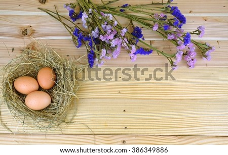 Chicken eggs in a nest decorate with pink and purple flowers on the wooden table.Easter festival  - stock photo