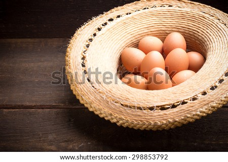chicken eggs in a strawhat on a wooden table - stock photo
