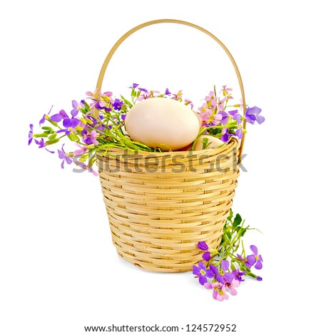 Chicken eggs in a wicker basket with pink and purple flowers isolated on white background