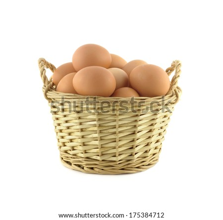 Chicken eggs in brown small handmade wicker basket isolated over white close up