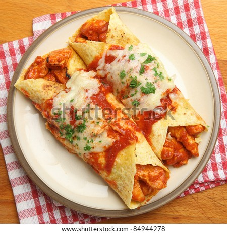 Chicken enchiladas with spicy tomato sauce and melted cheese. - stock photo