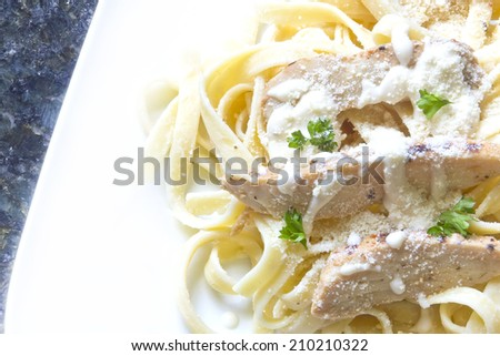Chicken Fettuccini alfredo with fresh curly parsley - stock photo