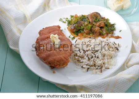 Chicken fillet in breadcrumbs garnished with rice and vegetables. - stock photo