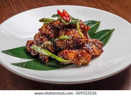 chicken fillet in tomato sauce with sesame seeds, chili - stock photo