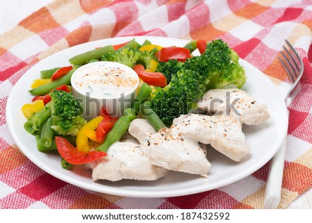 chicken fillet, steamed vegetables and yoghurt sauce, close-up