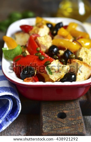 Chicken fillet stewed with bell pepper and capers on a rustic wooden background. - stock photo
