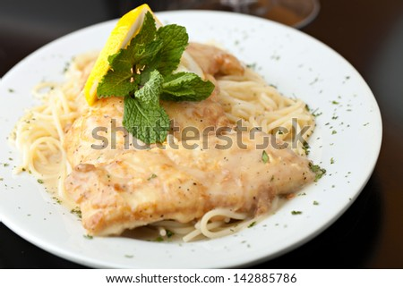 Chicken francaise or francese plated with pasta on a white dish. - stock photo