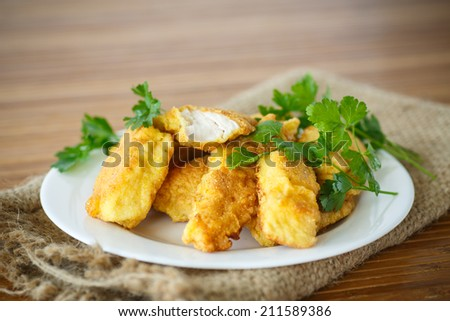 chicken fried in batter on a wooden table - stock photo