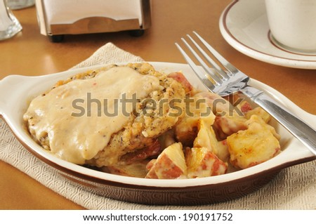 Chicken fried steak with country gravy and boiled red potatoes - stock photo