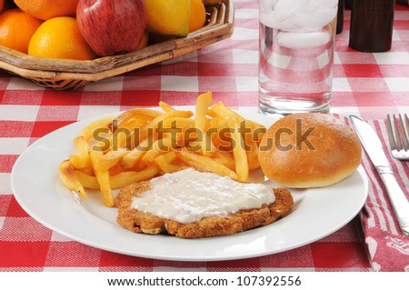 Chicken fried steak with fries and a basket of fruit - stock photo