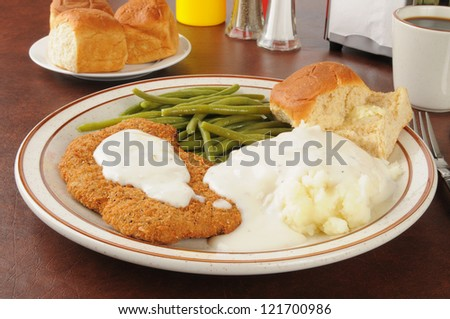 Chicken fried steak with mashed potatoes and country gravy - stock photo